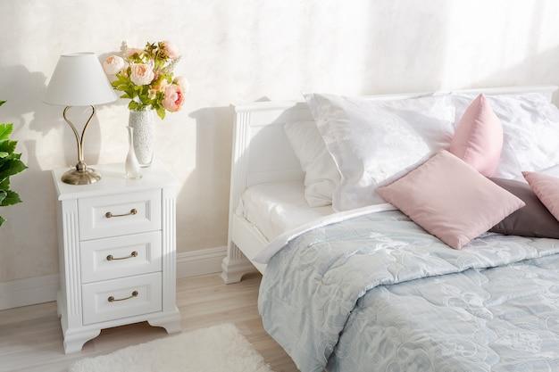 Quarto moderno e elegante com design minimalista em um interior luxuoso e caro de um apartamento em plano aberto em cores claras.