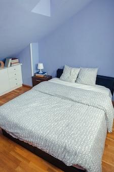 Quarto no sótão com cama de casal e cômoda com livros