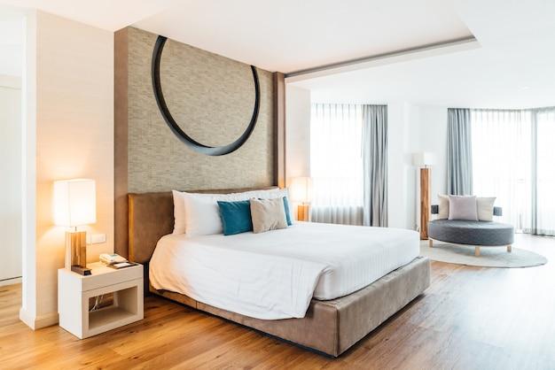 Quarto principal decorado com tons claros e quentes, cobertor branco, travesseiros azuis e cinzas.