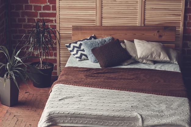 Quarto simples com cama de casal, parede de tijolo vermelho e grande janela