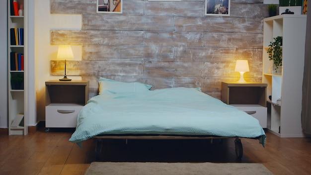 Quarto vazio com colchão confortável na cama. lâmpada elegante.