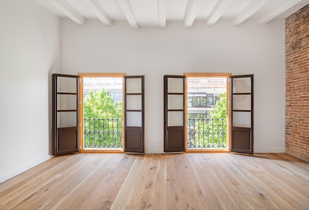 Quarto vazio, com piso de madeira e duas varandas