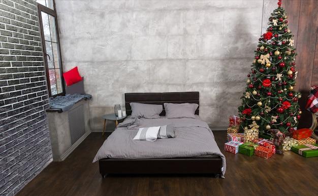 Quarto vazio moderno em estilo loft com cores cinza e árvore de natal com presentes, cama com cobertor cinza