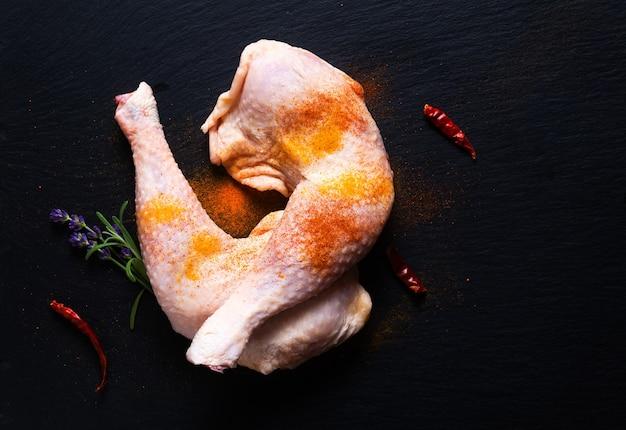 Quartos de frango crus de conceito de comida com especiarias em uma placa de pedra de ardósia preta com espaço de cópia