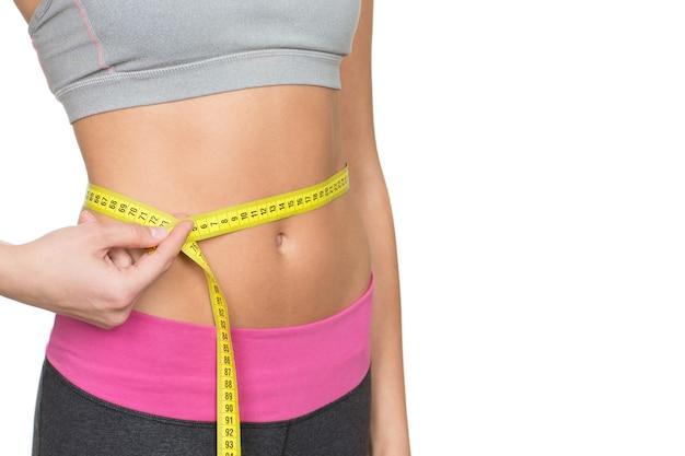 Quase perfeito. foto de close up recortada de uma mulher fitness com corpo tonificado e esportivo medindo a cintura na lateral