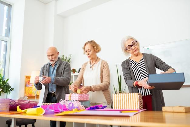 Quase pronto. idosos simpáticos olhando seus presentes enquanto os embrulham no papel de embrulho