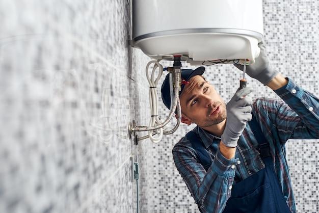 Quase pronto, o trabalhador instalou a caldeira de aquecimento elétrico no banheiro de casa