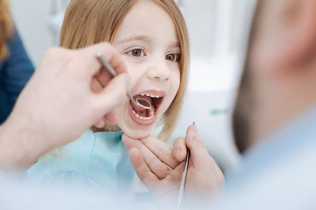 Quase sorrindo. menina emocionalmente ordenada e admirável se comportando como uma criança legal e mostrando seus dentes para o médico