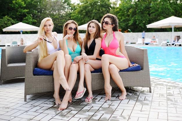 Quatro amigas atraentes de biquíni, sentado no sofá na piscina