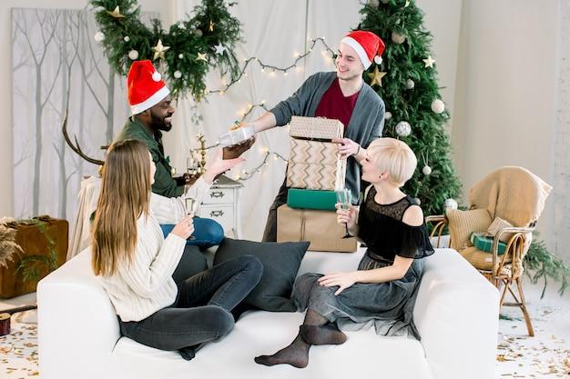 Quatro amigos multiétnicos felizes compartilhando presentes de natal
