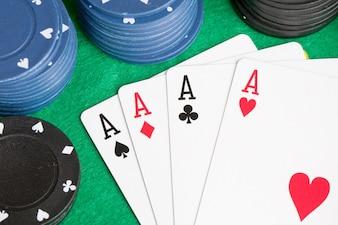 Quatro ases e fichas empilhadas de poker de muitas cores