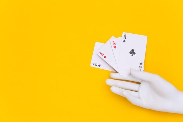 Quatro ases na mão do manequim em fundo amarelo