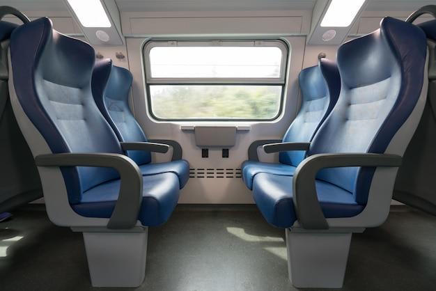 Quatro assentos azuis vazios de frente para o outro no trem europeu moderno
