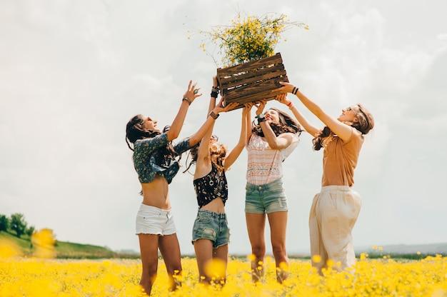 Quatro bela garota hippie em um campo de flores amarelas