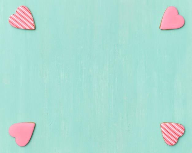 Quatro biscoitos de gengibre rosa em forma de coração nos cantos do fundo turquesa