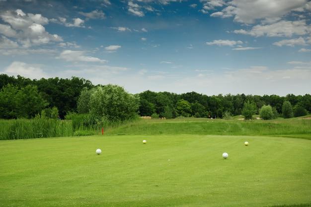 Quatro bolas coloridas no campo de golfe, plataforma de lançamento
