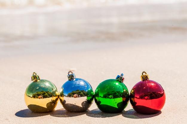 Quatro bolas de decoração de natal na areia da praia do mar