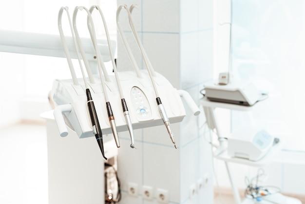 Quatro brocas dentais na cremalheira para o equipamento no escritório dental.