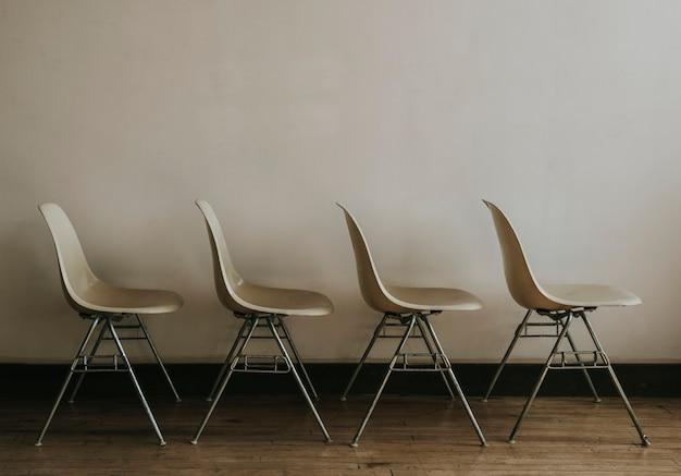 Quatro cadeiras brancas vazias em uma sala