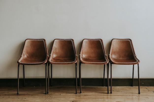 Quatro cadeiras marrons vazias em uma sala