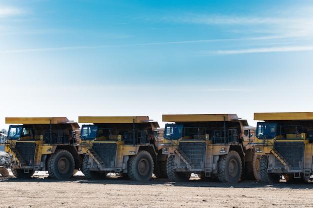 Quatro caminhões basculantes amarelos nos meus colocados em fila