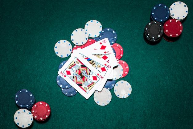 Quatro cartas de jogar mostrando um royal flush no diamante sobre as fichas do casino na mesa de poker verde