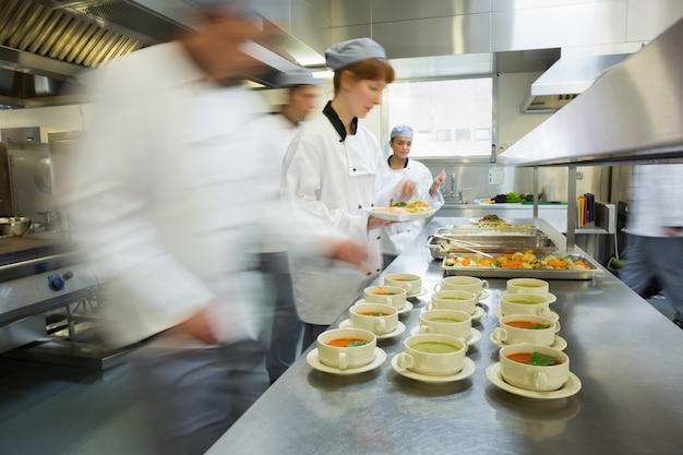 Quatro chefs trabalhando em uma cozinha moderna