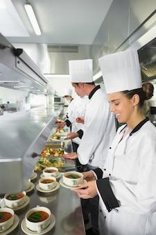 Quatro chefs trabalhando em uma cozinha ocupada