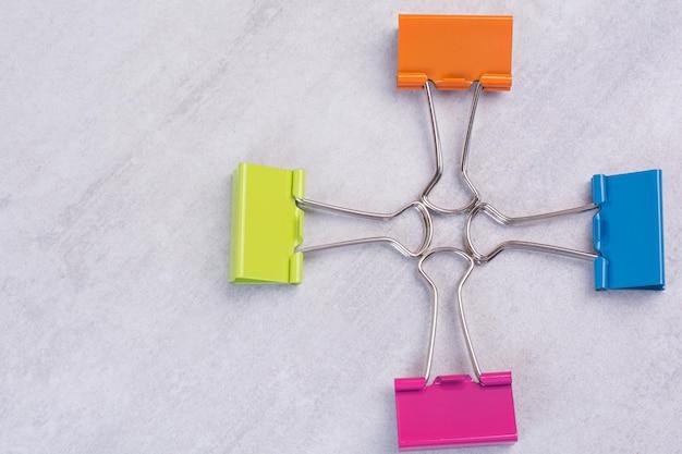 Quatro clipes de papel na superfície branca.