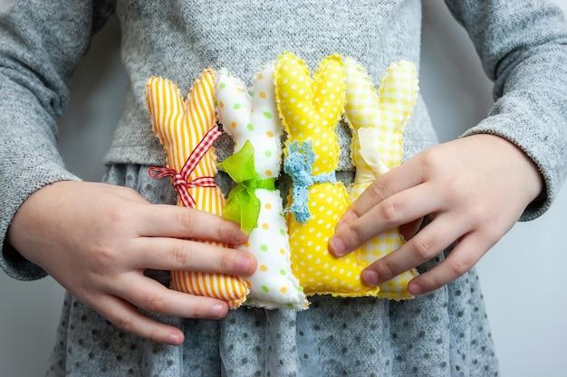 Quatro coelhinhos da páscoa coloridos e brilhantes feitos à mão nas mãos de uma menina com roupas cinza
