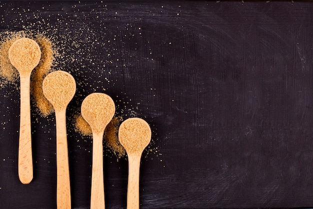 Quatro colheres de madeira com açúcar de bastão marrom no fundo preto.