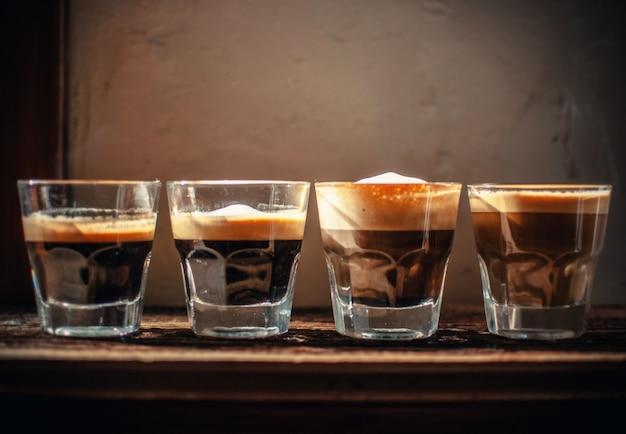 Quatro copos com licor enfileirados