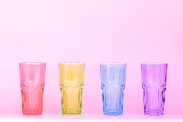 Quatro copos de vidro idênticos: vermelho, verde, azul, roxo.