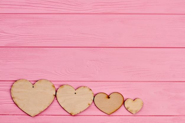 Quatro corações de madeira compensada em fundo colorido. linha de corações de madeira no fundo rosa de madeira com espaço de cópia. cartão de dia dos namorados.