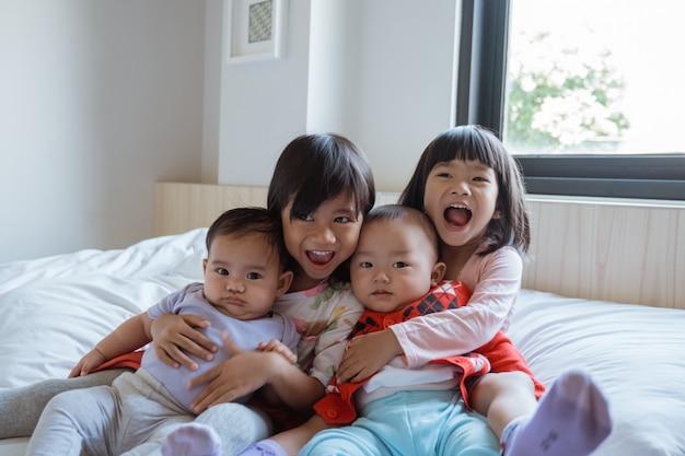 Quatro crianças felizes em brincar e brincar na cama