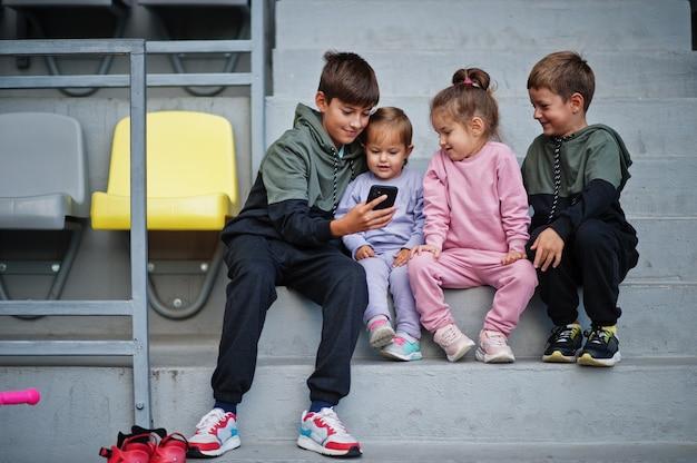 Quatro crianças lindas sentadas na área de esporte e olhando para o celular.