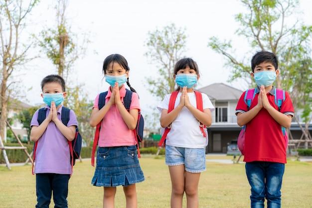 Quatro crianças pré-escolares de crianças asiáticas se encontram no parque da escola com as próprias mãos. em vez de cumprimentar com um abraço ou um aperto de mão, eles respeitam.