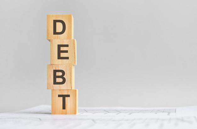 Quatro cubos de madeira com a palavra dívida no fundo das demonstrações financeiras brancas, forte conceito de negócio. fundo cinza