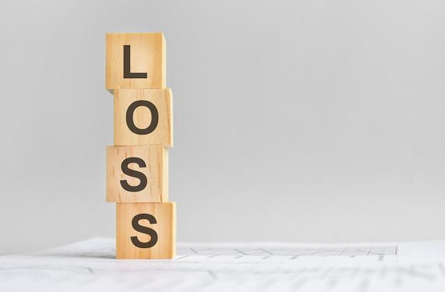 Quatro cubos de madeira com a palavra perda no fundo de marcos financeiros brancos, forte conceito de negócio