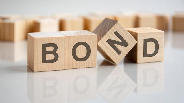 Quatro cubos de madeira com as letras bond na superfície brilhante de uma mesa cinza, conceito de negócio