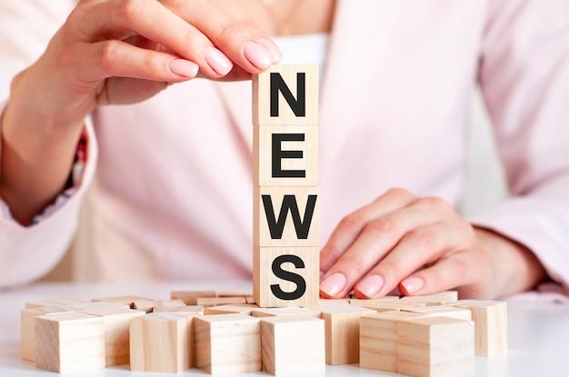 Quatro cubos de madeira com notícias de palavras, na superfície de mãos femininas com roupas rosa