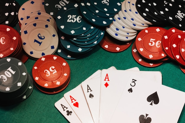 Quatro de um tipo de ases no pôquer na mesa de jogo com fichas
