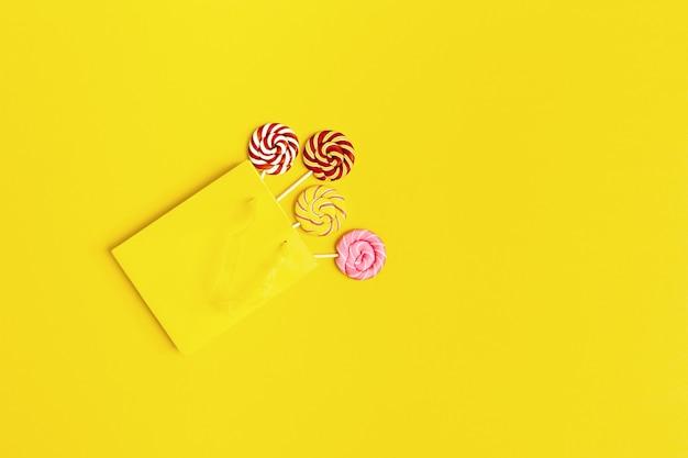 Quatro doces pirulito em saco de papel amarelo brilhante com espaço de cópia. rodada de doces na vara. alimento mínimo do açúcar da vida. composição plana leiga.