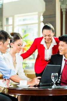 Quatro empresários chineses asiáticos ou empresários e empresárias em reunião de negócios no saguão de um hotel discutindo documentos em um tablet enquanto bebem café