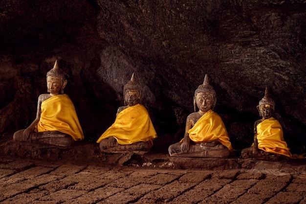 Quatro estátuas antigas de buda em uma caverna na província de chumphon, tailândia