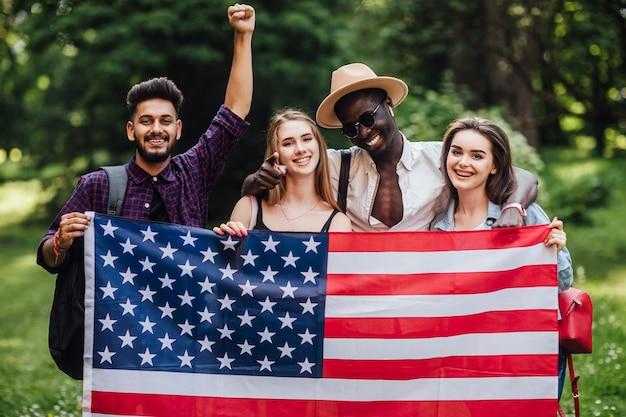 Quatro estudantes americanos com bandeira em universidade no campus