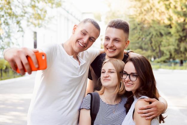 Quatro estudantes tomando selfie com celular vermelho no parque no campus da universidade