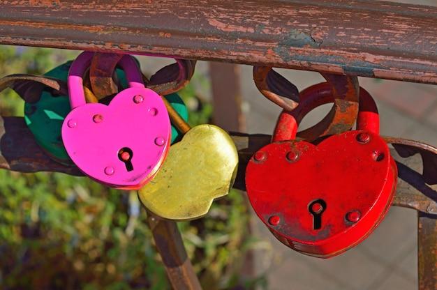 Quatro fechaduras em forma de coração estão penduradas na grade da ponte