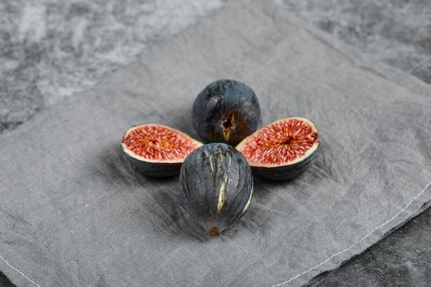 Quatro figos pretos em uma superfície de mármore com uma toalha de mesa cinza