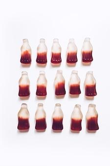 Quatro filas de fundo de balas de goma com sabor a cola e em forma de garrafa